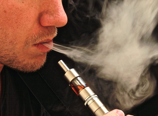 Man exhaling vapor from e-cig