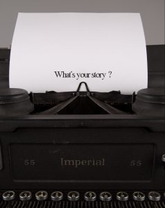 "Photo of antique typewriter holding a sheet of paper that has ""What's your story"" typed on it"